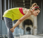 Active woman catching breath after exercise on bridge in Paris Royalty Free Stock Photos