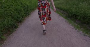 Active woman in colorful dress walking on gravel way. Handheld shot. Active woman in colorful dress walking on gravel way. Handheld follow shot stock footage