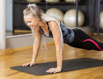 Active Woman Doing Pushups On Mat In Gym Stock Images