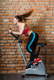 Active woman doing sport biking. Active young woman working out, doing sport biking in the gym for fitness. Sporty girl training in club. Slim body weight loss Royalty Free Stock Images