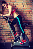 Active woman doing sport biking. Active young woman working out, doing sport biking in the gym for fitness. Sporty girl training in club. Slim body weight loss Stock Photography