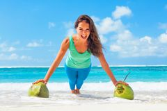 Active woman doing sports exercises with coconuts on sea beach royalty free stock photo