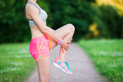 Active woman doing warm-up routine in the park before running, stretching leg muscles with standing single knee to chest Stock Photography
