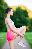 Active woman doing warm-up routine in the park before running, stretching leg muscles with standing single knee to chest. Fitness runner body closeup doing warm Royalty Free Stock Images