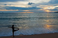 Active woman doing yoga on the beach at sunset Stock Photography