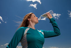 Active woman drinking from water bottle. Stock Image