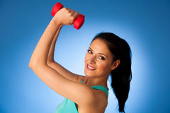 Active woman with dumbbells workout in fitness gym over blue bac Royalty Free Stock Image