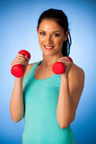 Active woman with dumbbells workout in fitness gym over blue bac Stock Photos