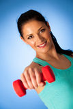 Active woman with dumbbells workout in fitness gym over blue bac Stock Photography