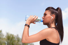 Active Woman With Earbuds  Drinking Water Stock Photography
