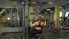 An active woman is engaged in sports for the development of pectoral muscles. stock video