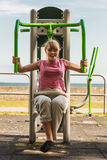 Active woman exercising on chest press outdoor. Royalty Free Stock Photos