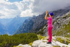 Active woman exercising in the nature above the beautiful valley. Yoga and meditation in the mountains with view. Active lifestyle - healthy lifestyle Royalty Free Stock Images