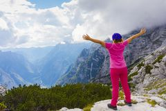 Active woman exercising in the nature above the beautiful valley. Yoga and meditation in the mountains with view. Active lifestyle - healthy lifestyle royalty free stock image