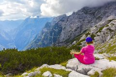 Active woman exercising in the nature above the beautiful valley. Yoga and meditation in the mountains with view. Active lifestyle - healthy lifestyle Stock Photos