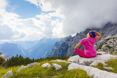 Active woman exercising in the nature above the beautiful valley. Yoga and meditation in the mountains with view. Active lifestyle - healthy lifestyle stock image