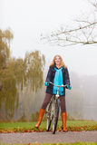 Active woman having fun riding bike in autumn park Stock Photo