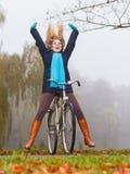 Active woman having fun riding bike in autumn park Stock Photos