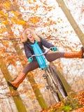 Active woman having fun riding bike in autumn park Stock Photography