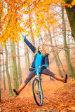 Active woman having fun riding bike in autumn park. Happy carefree active woman having fun riding bike bicycle in fall autumn park. Crazy young girl relaxing Royalty Free Stock Images