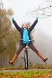 Active woman having fun riding bike in autumn park. Happy carefree active woman having fun riding bike bicycle in fall autumn park. Crazy young girl relaxing Stock Photography