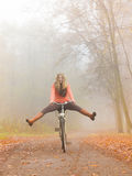 Active woman having fun riding bike in autumn park. Happy carefree active woman having fun riding bike bicycle in fall autumn park. Crazy young girl in sweater Stock Photo