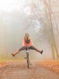 Active woman having fun riding bike in autumn park Stock Photo