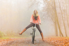 Active woman having fun riding bike in autumn park. Happy carefree active woman having fun riding bike bicycle in fall autumn park. Crazy young girl in sweater Royalty Free Stock Photo