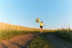 Active woman having fun on summer vacation. Happy girl jumping with colorful balloons against blue sky background. Active woman having fun on summer vacation royalty free stock photography