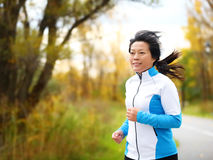 Active woman in her 50s running and jogging. Middle aged Asian mature female jogger outdoor living healthy lifestyle in beautiful autumn city park in colorful royalty free stock images