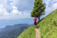 Active woman hiking in the mountains above the valley Royalty Free Stock Photo