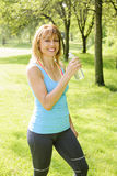 Active woman holding water bottle outside Stock Photo