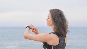 Woman jogger doing exercises and looking data on fitness smart watch