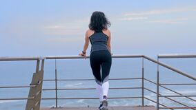 Active woman jogger on the seashore doing sport exercises, Fitness cross fit and sports concept