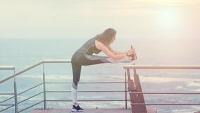 Active woman jogger on the seashore doing sport exercises, sports concept