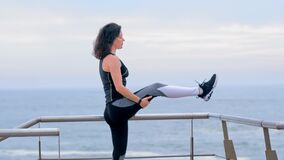 Active woman jogger on the seashore doing stretching exercises for legs