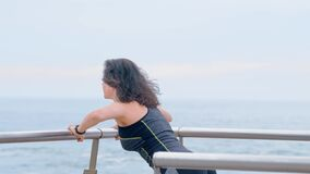 Active woman jogger on the seashore doing sport exercises