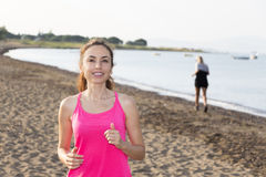 Active woman jogging by a beach Stock Photos
