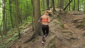 Sporty And Active Pretty Woman Running On Forest Path Uphill, Back View. Active woman with long hair. In the orange top and leggings, headphones and a phone on stock footage