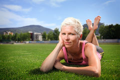 Active woman lying on green grass royalty free stock image