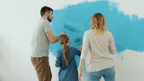 Active woman man and little girl painting house walls and dancing having fun at home