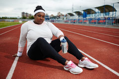 Active woman. Plus-size woman in sportswear sitting on racetrack Stock Images