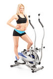 Active woman posing on a cross trainer machine Royalty Free Stock Image