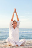 Active woman practicing yoga on the beach Stock Photography