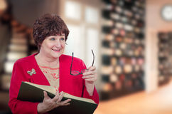 Active woman professor laughs with book. Portrait of smiling senior female professor reads big book with blurred library in background. Aged woman is laughing stock image