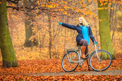 Active woman riding bike in autumn park. Stock Image