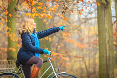 Active woman riding bike in autumn park. Stock Photos