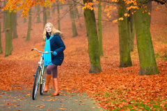 Active woman riding bike in autumn park. Active woman riding bike bicycle in fall autumn park. Young girl in jacket and scarf relaxing. Healthy lifestyle and Royalty Free Stock Photos