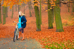 Active woman riding bike in autumn park. Active woman riding bike bicycle in fall autumn park. Young girl in jacket and scarf relaxing. Healthy lifestyle and Royalty Free Stock Images