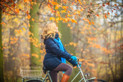 Active woman riding bike in autumn park. Active woman riding bike bicycle in fall autumn park. Young girl in jacket and scarf relaxing. Healthy lifestyle and Royalty Free Stock Photography